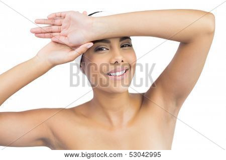 Happy nude brunette with hairband touching forehead on white background