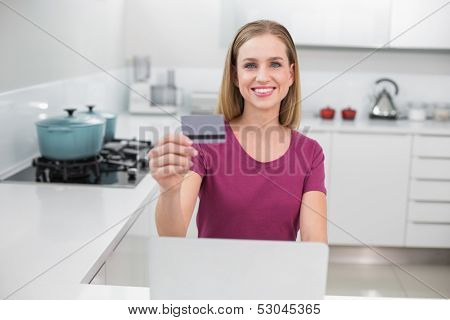 Gleeful casual woman using laptop and credit card sitting in kitchen