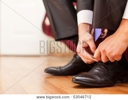 Man is tying his shoes