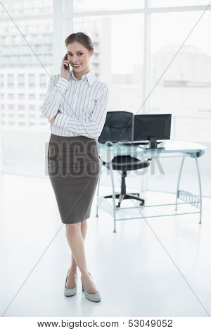 Gleeful calm businesswoman phoning with her smartphone standing in her office smiling at camera