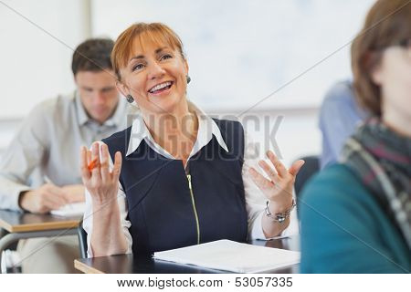 Laughing female mature woman sitting in classroom talking to her teacher