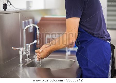 Kitchen porter washing his hands in professional kitchen