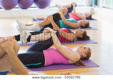 Sporty people doing the supine wind release posture on mats at yoga class in fitness studio