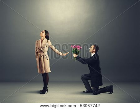 young beautiful woman don't looking at man with flowers