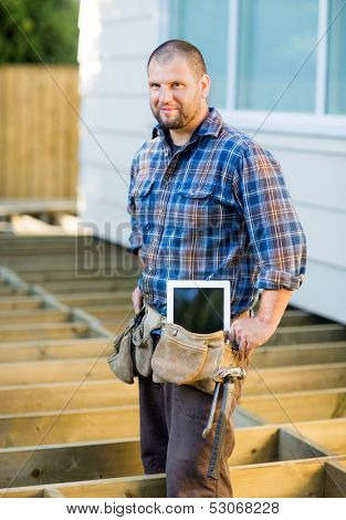 Portrait of confident mid adult manual worker with digital tablet and hammer in tool belt at construction site