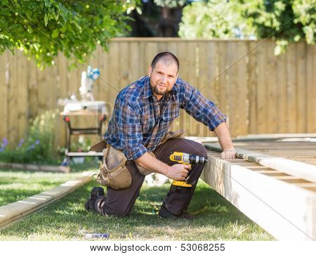 Full length portrait of manual worker drilling wood at construction site