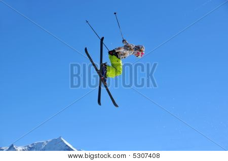 Girl Skier  Performing A High Jump With Crossed Skis