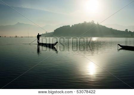 sunrise on lake,fisherman rowing the boat