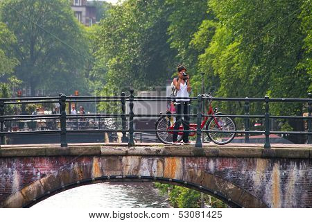 AMSTERDAM - JULY 17: Woman take pictures standing near bicycle on bridge. Bicycles are most used mode of transport and very popular with tourists and locals in Amsterdam, Netherlands on July 15, 2007.