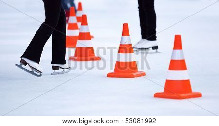 Girl Ice Skaters Legs And Red White Striped Cones On The Ice Rink