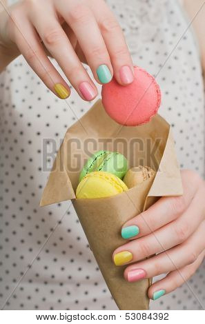 Colorful french dessert macaroons in the hands of girl