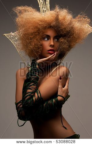 beaut, glamour and helloween concept - woman with long curly hair in crown