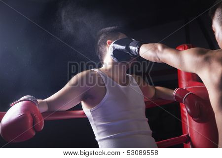 Male boxer throwing knockout punch in the boxing ring