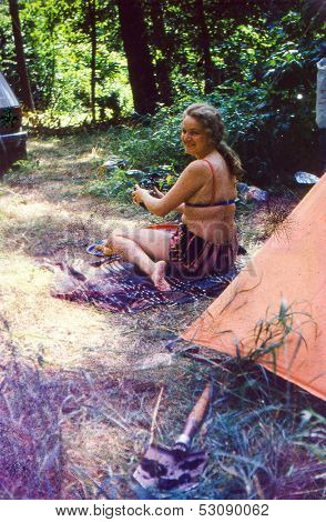 Vintage photo (scanned reversal film) - young woman preparing food on camping, seventies