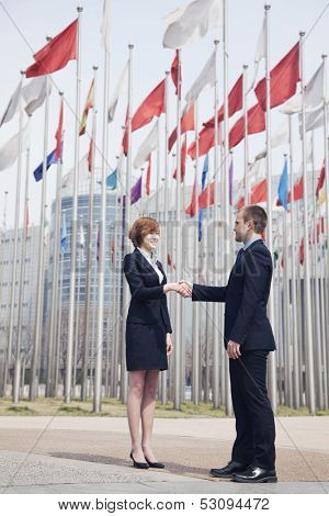 Two business people shaking hands with flags flying in the background