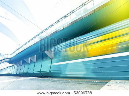Perspective wide angle view of modern light blue illuminated and spacious public metro marble station with fast blurred trail of vivid yellow train in vanishing traffic motion