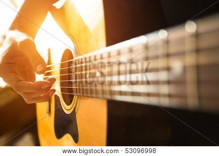 Female hand close-up playing on acoustic guitar.