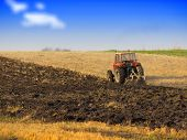stock photo of plow  - Red Tractor Plowing in Autumn - JPG