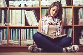 stock photo of short legs  - Full length of a female student sitting against bookshelf and reading a book on the library floor - JPG
