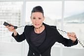 Frustrated young elegant businesswoman with telephone cable around her neck at a bright office