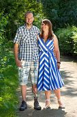 picture of amputee  - Handsome disabled man wearing an artificial leg standing arm in arm with an attractive woman outdoors in the countryside smiling at the camera with happy smiles - JPG