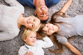 Close-up of happy family lying on carpet and looking up