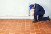 Handyman in blue boiler suit repairing a radiator in bright room