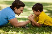 pic of wrestling  - Cute boy trying to beat his dad in arm wrestling while having fun together in a park - JPG