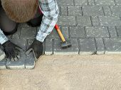 stock photo of laying-in-bed  - Paver laying driveway pavement out of concrete pavement blocks - JPG