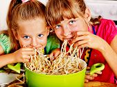 image of pinafore  - Children  eating spaghetti at kitchen - JPG