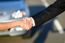 stock photo of rental agreement  - Man and woman closing a car sale agreement with a handshake - JPG