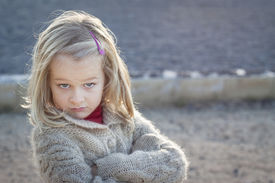 image of cheeky  - A small girl with crossed arms and a cheeky attitude looking at the camera  - JPG