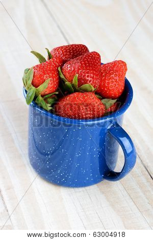 A blue speckled cup on a rustic farmhouse style kitchen table filled with freshly picked ripe strawberries. Vertical format.