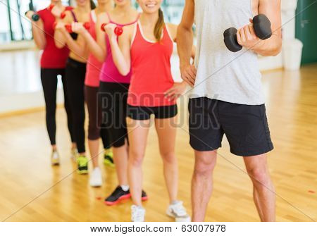 fitness, sport, training, gym and lifestyle concept - group of people working out with dumbbells in the gym