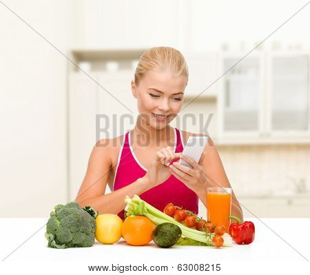 dieting, food, healthcare and technology concept - smiling sporty woman with fruits and vegetables counting calories in smartphone