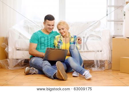 moving, home, technology and couple concept - smiling couple with laptop sitting on floor in new house