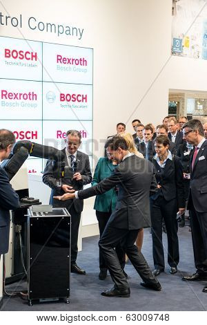 HANOVER, GERMANY - APRIL 7: German Chancellor Angela Merkel during a technology showcase tour of industrial Robotics by Bosch and Rexroth at the Hannover Messe, 7 April 2014