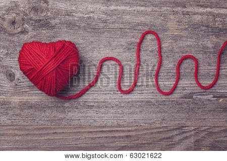 Red heart of red wool yarn on a wooden background