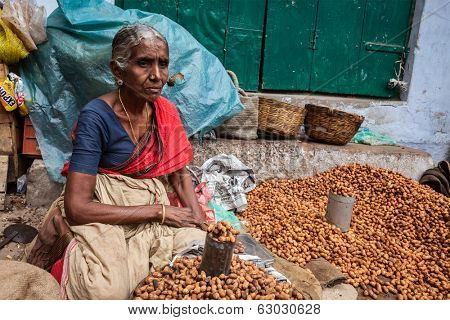 TIRUCHIRAPALLI, INDIA - FEBRUARY 14, 2013: Unidentified Indian woman - hawker (street vendor) of fried peanuts