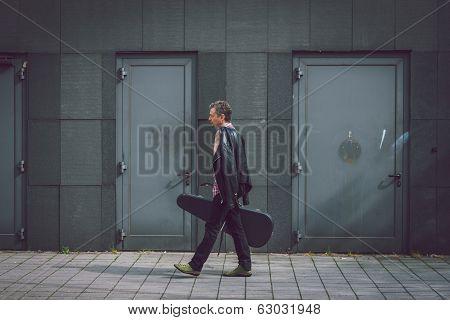 Man In Short Sleeve Shirt Walking With Guitar Case