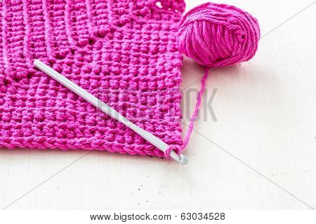 Homemade crochet dishcloths made of vibrant colored yarn. Crochet hook and a ball of yarn is along side.