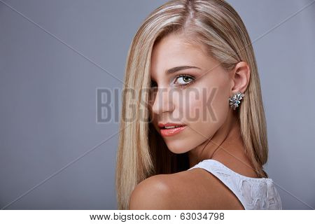 Portrait of a pretty tanned young woman with long blond hair and green eyes on gray background