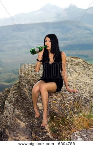 Young Woman With A Champagne Bottle Sits On A Rock