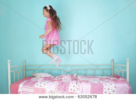 8 years old girl jumping on the bed at home