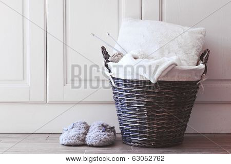 Wicker basket with warm blanket and knitting in it and soft slippers near it