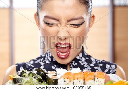 Beautiful sushi woman showing a plate of sushi.