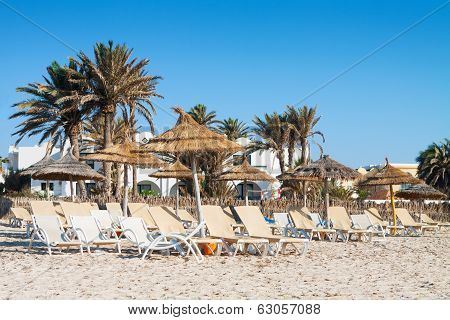Sandy Beach With Deckchairs And Parasols