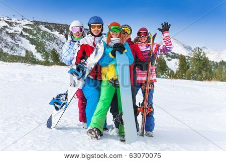 Happy friends with snowboards and skis