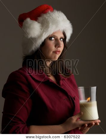 Serene young woman in Santa hat holds a lit candle; isolated