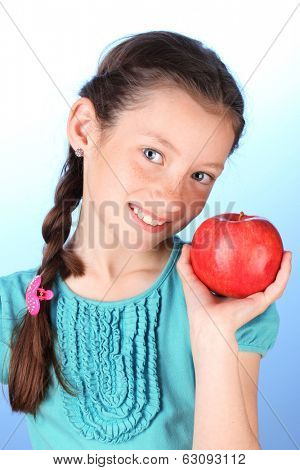 Portrait of beautiful little girl with apple on blue background